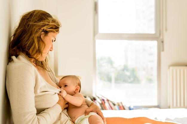Bebé amamantado por su madre en la cama tranquila por la mañana, concepto de maternidad saludable. Foto Premium