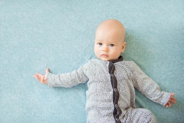 Bebé curioso tranquilo acostado, vista superior Foto Premium