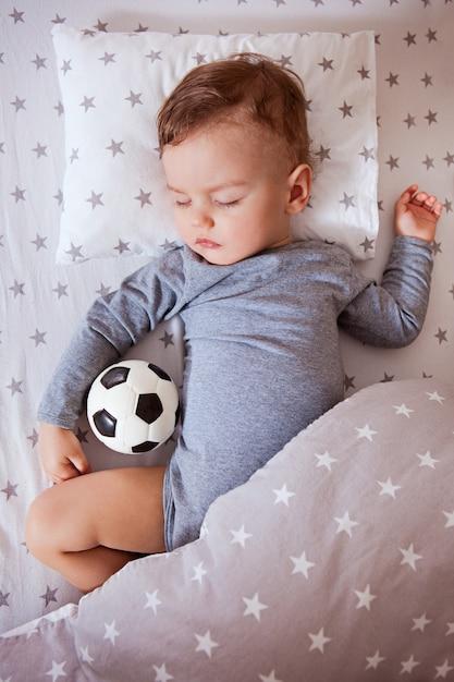 El bebé está durmiendo en una cuna con una pelota de fútbol en la mano. Foto Premium
