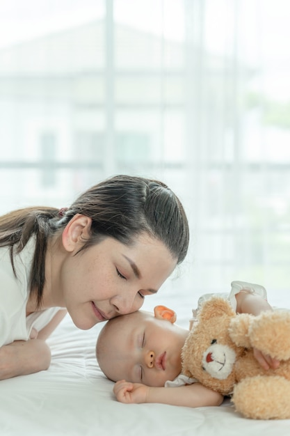 Bebé durmiendo con un oso de peluche y madre cuidando de ellos Foto gratis