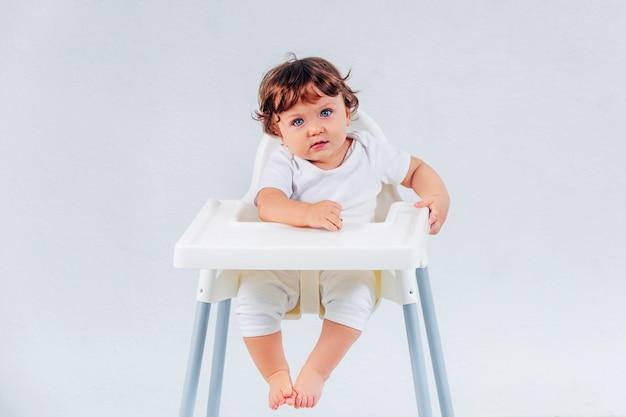 Bebé feliz que se sienta en fondo del estudio Foto gratis