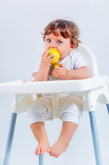 Bebé feliz sentado y comiendo Foto gratis