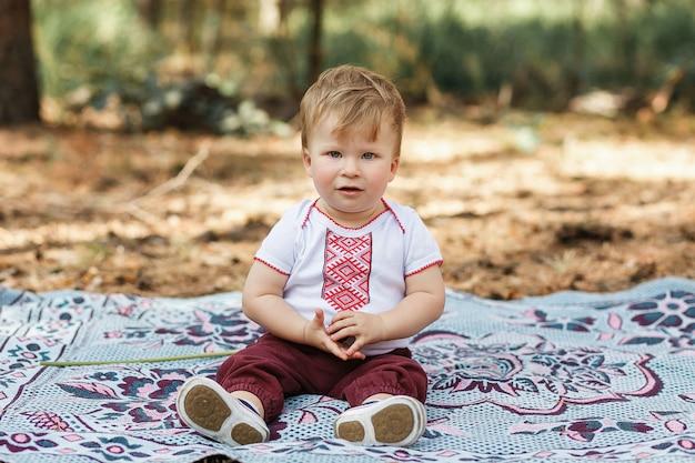 Bebé hermoso un año que se sienta en la tierra. el niño se divierte en el bosque de primavera Foto gratis