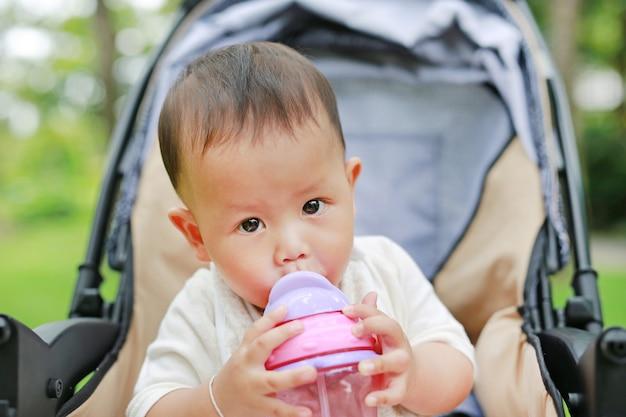 Bebé infantil en cochecito y agua potable de una taza para bebés con pajita Foto Premium