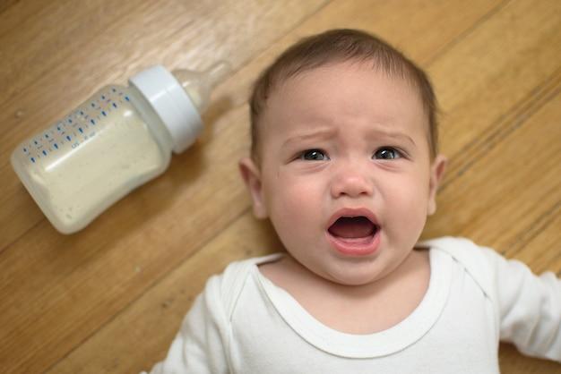 Bebé está llorando en el suelo con la botella de fórmula Foto Premium
