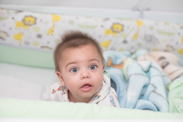 8e9710f59 Bebé de ojos azules acostado en la cuna | Descargar Fotos premium