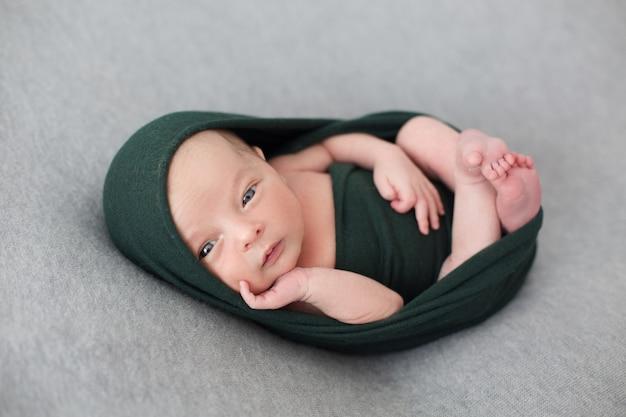 Un bebé pequeño envuelto con tejido negro streth. Foto gratis