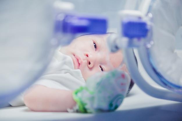 Bebé recién nacido cubierto de vertix dentro de incubadora. Foto Premium