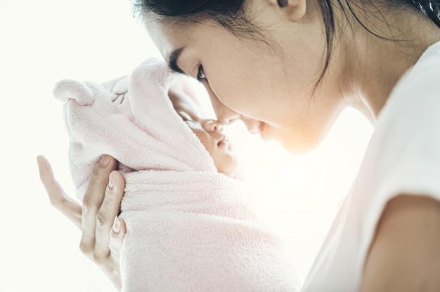 Bebé recién nacido durmiendo en manos de la madre y la nariz chocó Foto gratis