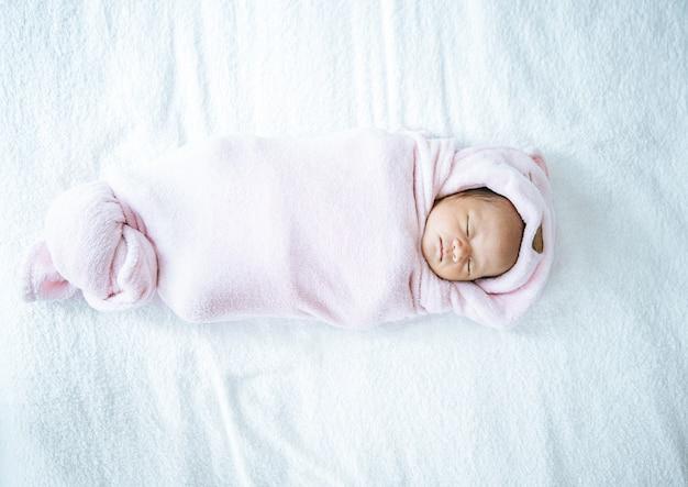 Bebé recién nacido durmiendo en una manta rosa suave Foto gratis