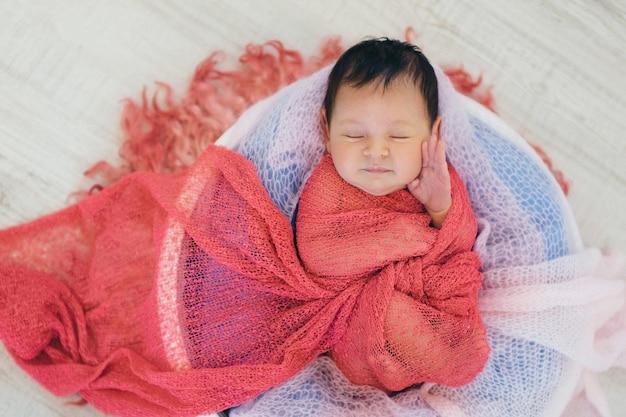 Bebé recién nacido envuelto en una manta durmiendo en una canasta. concepto de infancia, asistencia sanitaria, fiv Foto Premium