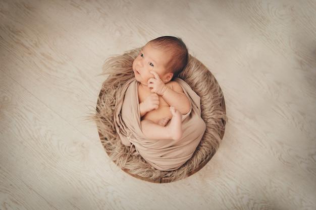 Bebé recién nacido envuelto en una manta durmiendo en una canasta. concepto de infancia, asistencia sanitaria, fiv. Foto Premium