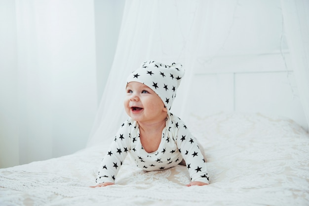 Bebé recién nacido vestido con un traje blanco y estrellas negras es una cama blanca suave en el estudio Foto Premium