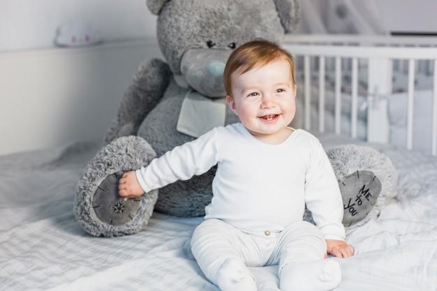 Bebé rubio adorable sobre cama blanca con oso de peluche Foto gratis