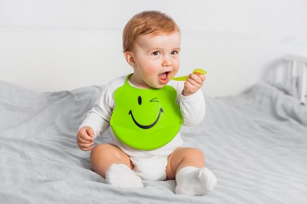 Bebé sentado con babero puesto Foto gratis