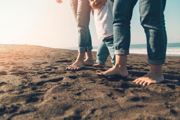 Bebé sonriente haciendo los primeros pasos con los padres en la playa soleada Foto gratis
