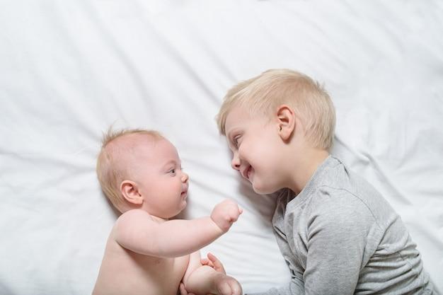 Bebé y sonriente hermano mayor están acostados en la cama. juegan, se comunican e interactúan. vista superior Foto Premium