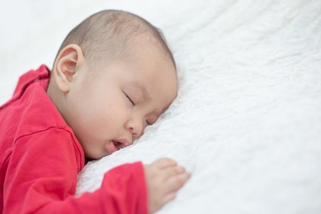 Bebés vestidos con camisas rojas durmiendo en la cama Foto gratis