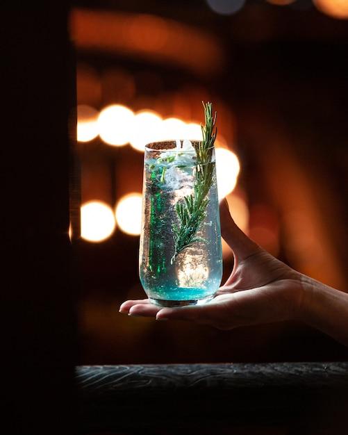 Bebida de alcohol blanco azul con una rama de romero en la mano. Foto gratis
