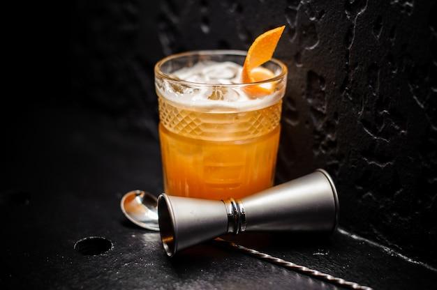 Bebida alcohólica de naranja fresca con hielo y piel de naranja Foto Premium