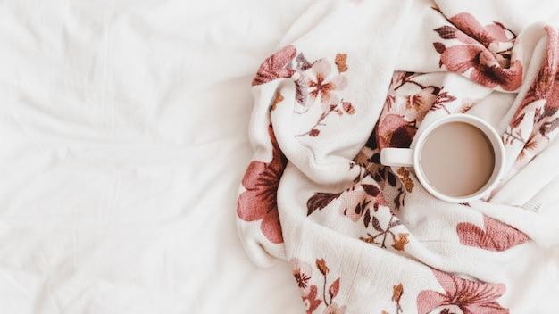 Bebida caliente en hermosa tela escocesa estampada en sábana Foto gratis