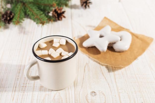 Bebida caliente de navidad con malvaviscos en una taza de hierro y galletas de jengibre, sobre una mesa blanca. Foto Premium