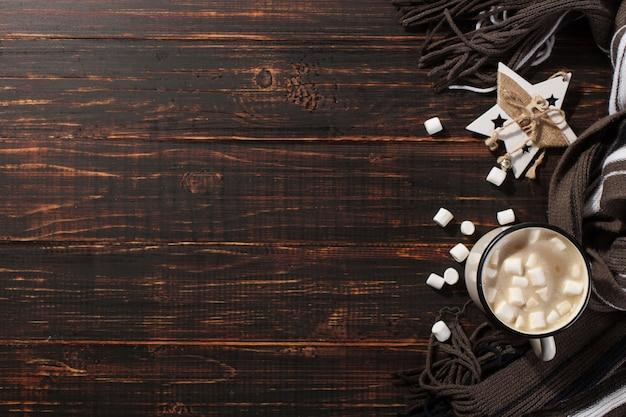 Bebida caliente de navidad con malvaviscos en una taza de hierro, sobre una mesa de madera y una bufanda. , vacaciones, tarjeta de felicitación copyspace. Foto Premium