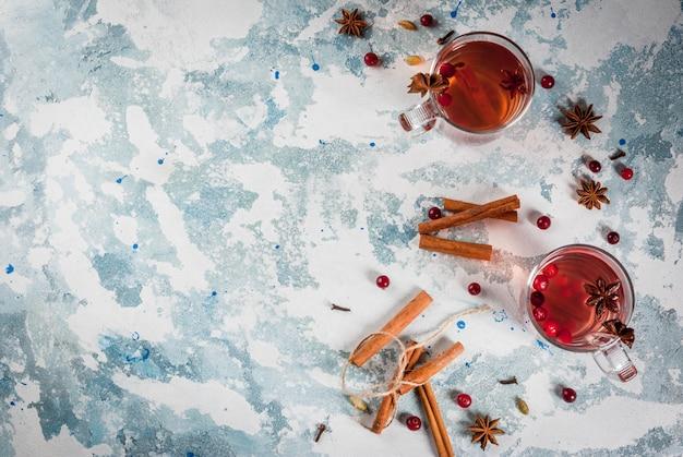 Bebida caliente de otoño, té especiado de frutas con arándano, canela, anís. en la mesa de hormigón azul claro, con vista superior de copyspace de ingredientes Foto Premium