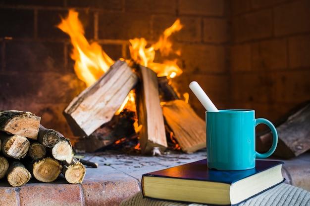 Bebida y libro junto a la chimenea.