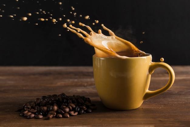 Bebida salpicando de la taza cerca de los granos de café Foto gratis