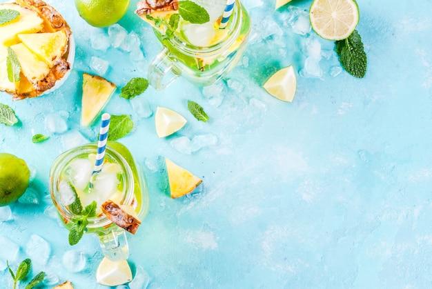 Bebida tropical mojito de piña o limonada con lima fresca y menta fondo azul claro Foto Premium
