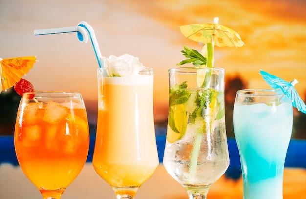 Bebidas amarillas suaves de naranja con rodajas de fresa y menta en vasos Foto gratis