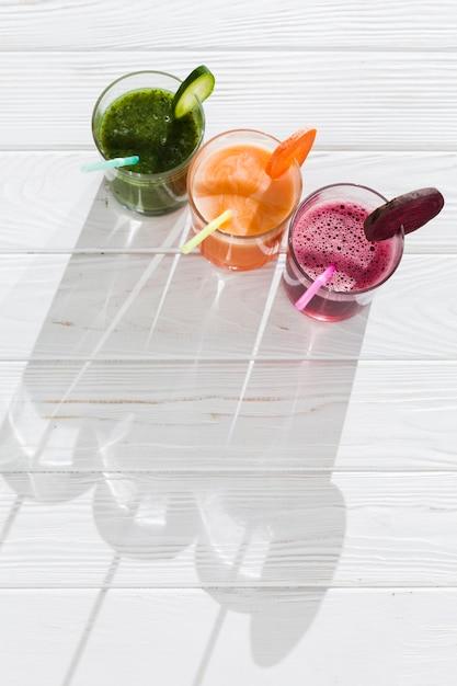 Bebidas coloridas en copas en mesa de madera Foto gratis