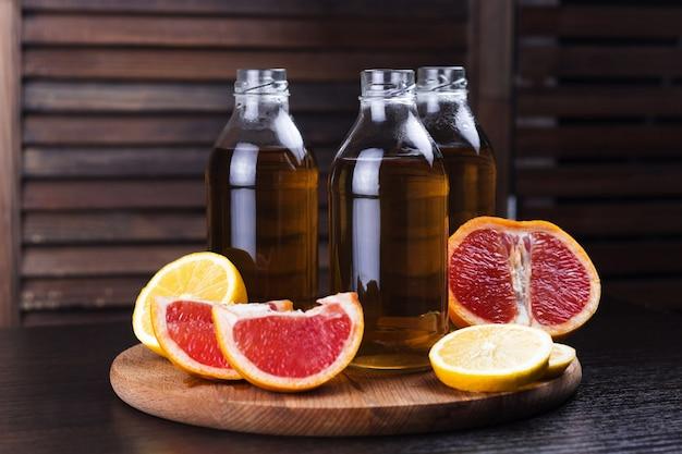 Bebidas frescas de limón y pomelo en botellas de vidrio. Foto Premium