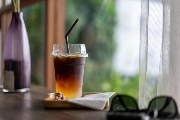 Bebidas frías de café negro colocadas en una mesa de madera Foto Premium