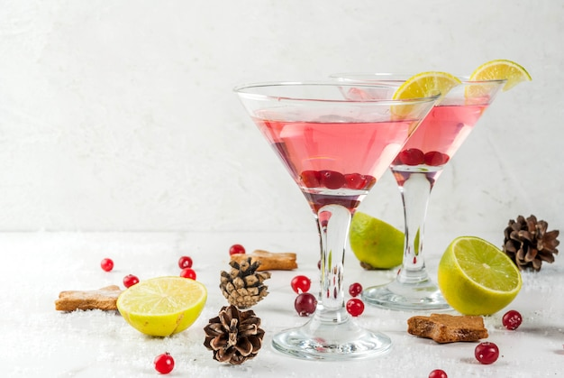 Bebidas de otoño e invierno. bebida navideña. martini arándano festivo con limón. en la mesa blanca con decoración de navidad, copyspace Foto Premium