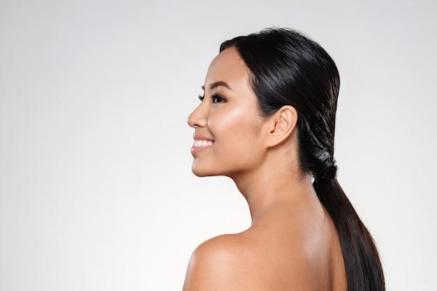 Bella dama asiática sonriente mirando a un lado Foto gratis