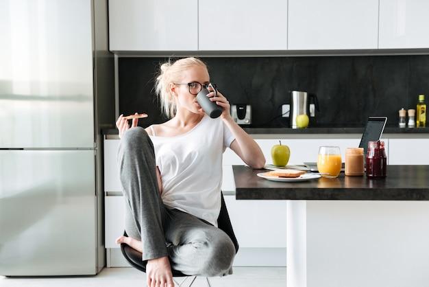 Bella dama bebiendo té y comiendo pan con mermelada en la mañana Foto gratis