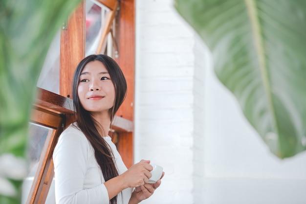 Una bella mujer con una camisa blanca de manga larga sentada en una cafetería. Foto gratis