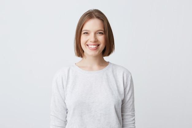 Bella mujer expresa emociones felices, tiene una amplia sonrisa agradable, viste manga larga blanca y se siente satisfecha Foto gratis