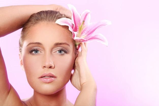 Bella mujer con flor de lirio Foto gratis