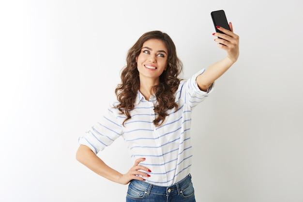 Bella mujer haciendo foto selfie en teléfono móvil, sonriendo, islolated, Foto gratis