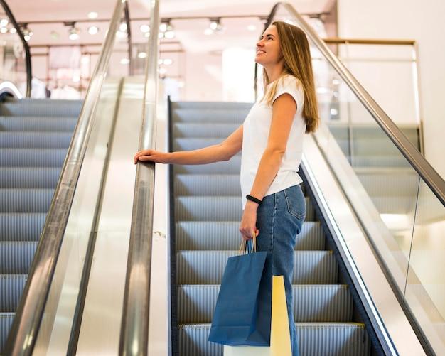 Bella mujer llevando bolsas de la compra. Foto gratis