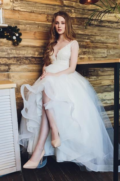 La bella mujer posando en un vestido de novia. Foto Premium