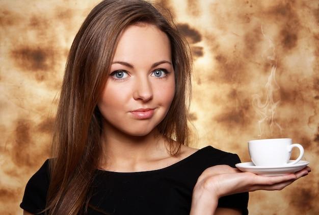 Bella mujer con una taza de café caliente Foto gratis