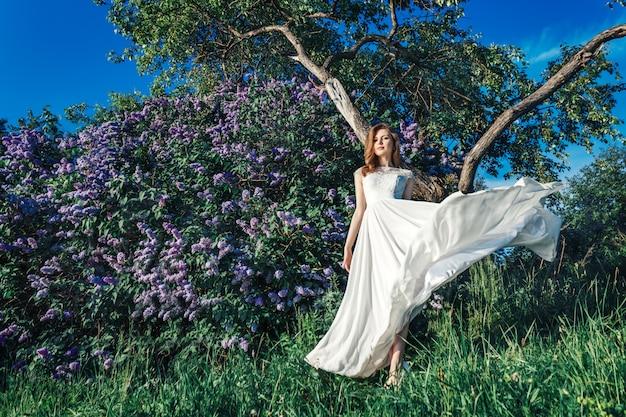 Una bella novia con flores lilas Foto Premium
