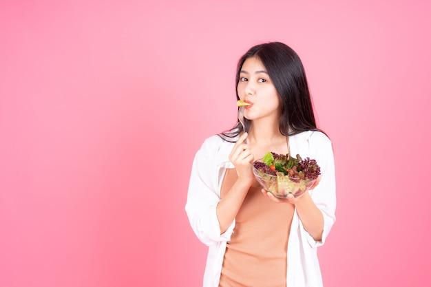 Belleza mujer asiática linda niña sentirse feliz comiendo dieta comida fresca ensalada para buena salud sobre fondo rosa Foto gratis