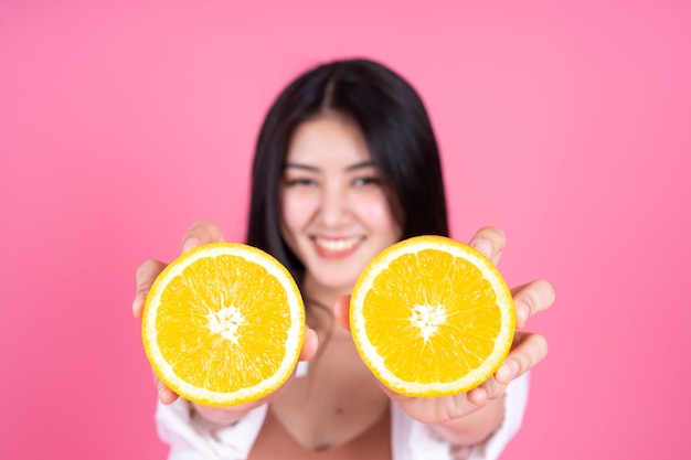 Belleza de la mujer asiática linda niña siente feliz holdind fruta naranja para una buena salud sobre fondo rosa Foto gratis