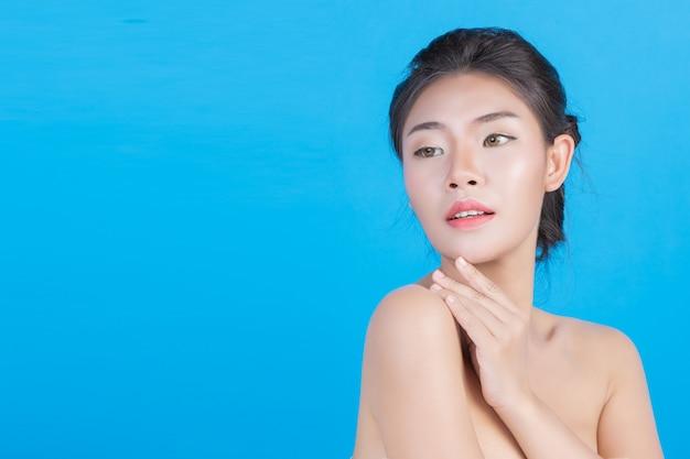 La belleza de las mujeres con imágenes perfectas de salud de la piel al tocar su rostro y sonreír como un spa para mimar su piel azul Foto gratis