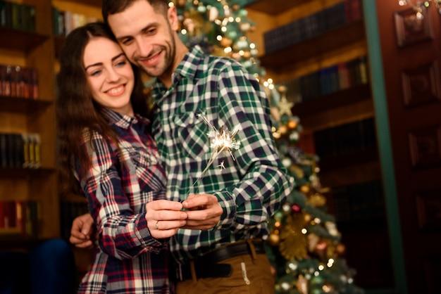 Bengalas y un beso para navidad! joven hermosa besador y quema de bengalas. pareja amorosa en navidad decorado habitación. Foto Premium